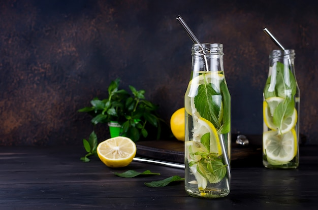 Frische mojito-getränke in flaschen und zutaten - zitrone und minze