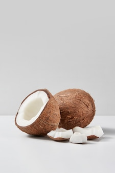 Frische natürliche organische reife ganze kokosnussfrucht mit der hälfte und den stücken auf einem hellgrauen duotonen hintergrund, kopienraum. vegetarisches konzept.