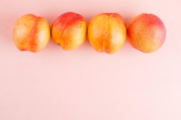 Frische nektarinen auf einer rosa oberfläche. flach liegen.