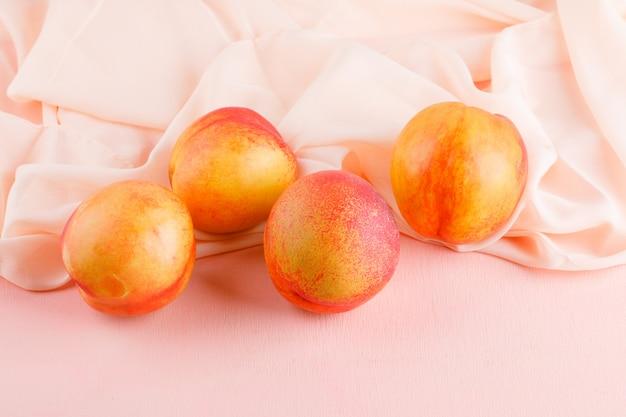 Frische nektarinen auf rosa und textiler oberfläche, hohe winkelansicht.