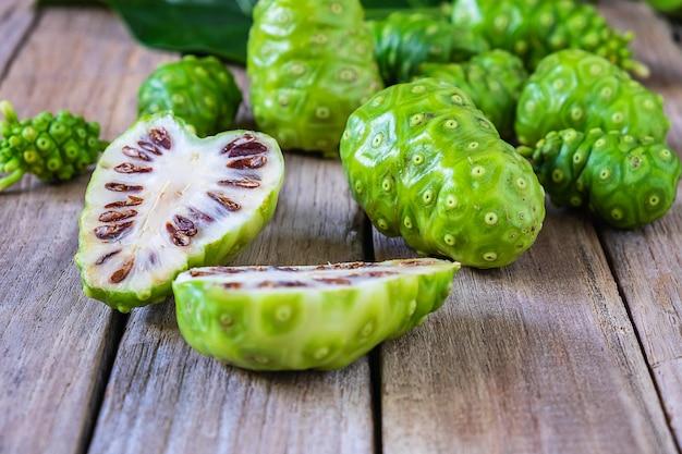 Frische noni-frucht auf einem hölzernen hintergrund