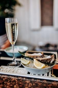 Frische offene austern mit einem glas gekühltem prosecco-wein serviert auf dem tisch. delikatessen mit meeresfrüchten
