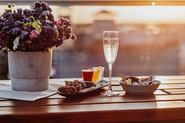 Frische offene austern mit einem glas gekühltem prosecco-wein und einer reihe von alkoholischen cocktails, die auf dem tisch serviert werden. delikatessen mit meeresfrüchten