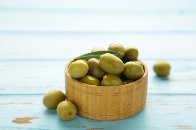Frische oliven in schüssel auf blauem hintergrund. ansicht von oben