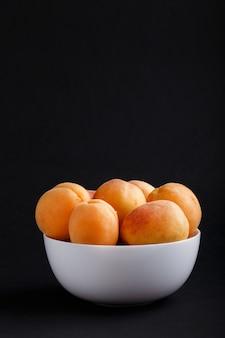Frische orange aprikosen in der weißen schüssel auf schwarzem copyspace. seitenansicht.