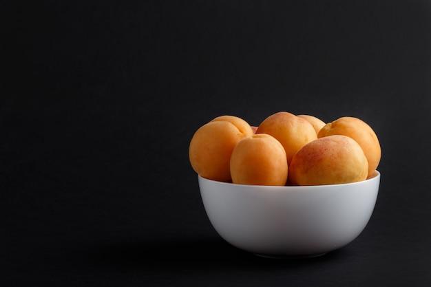 Frische orange aprikosen in der weißen schüssel auf schwarzem hintergrund