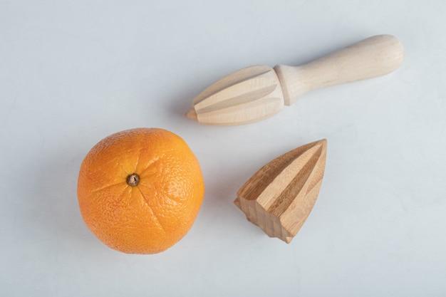 Frische orange frucht mit hölzernen reibahlen lokalisiert auf einem weißen hintergrund.