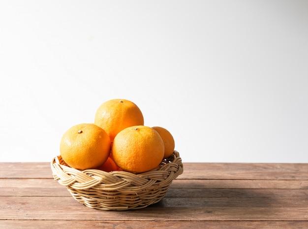 Frische orange früchte stellten in bambusbehälter auf hölzerner tabelle ein