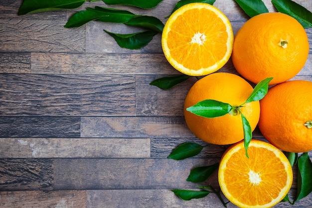 Frische orange und blätter auf hölzernem hintergrund