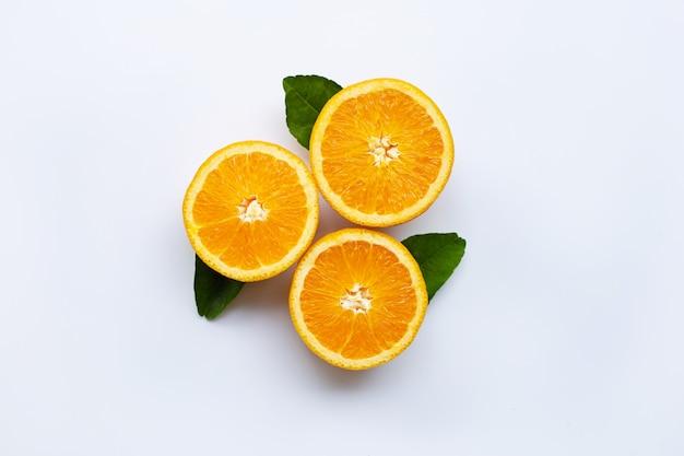 Frische orange zitrusfrucht mit den blättern lokalisiert auf weißem hölzernem hintergrund. draufsicht