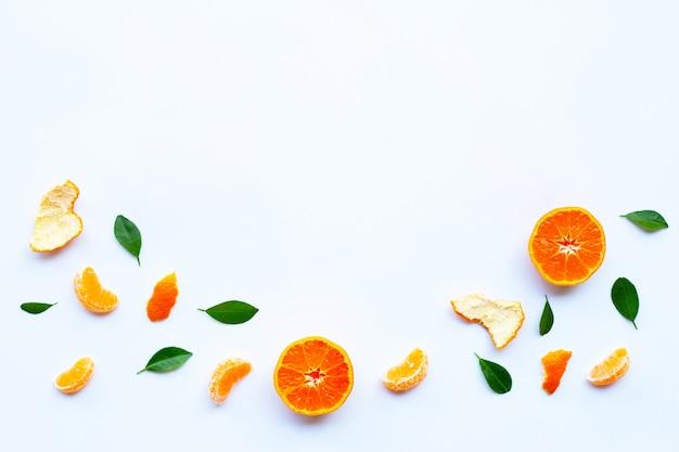 Frische orange zitrusfrucht mit grünen blättern auf weiß.