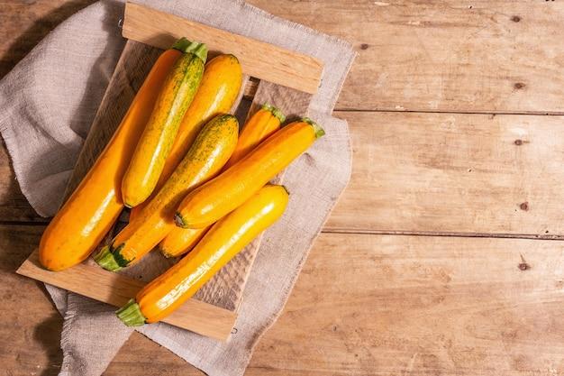 Frische orangefarbene zucchini. reifes gemüse ernten auf einem holzständer. vintage brettertisch, draufsicht