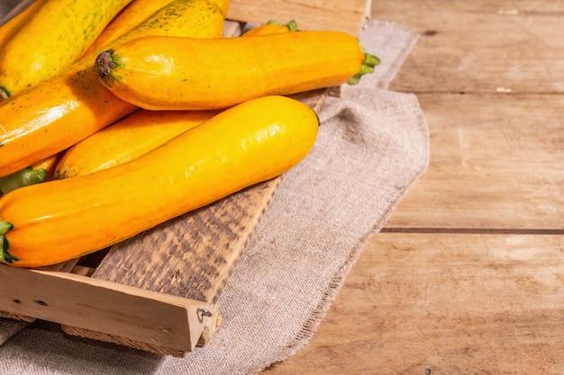 Frische orangefarbene zucchini. reifes gemüse ernten in einem holzständer. vintage bretter tisch, kopienraum