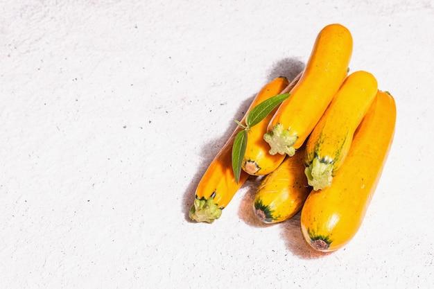 Frische orangefarbene zucchini. reifes gemüse ernten. trendiges hartes licht, dunkler schatten, weißer kitthintergrund, kopierraum