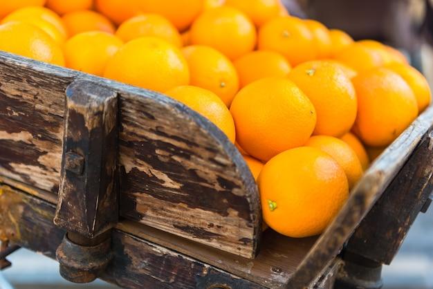 Frische orangen auf vintage holzkarren in der stadt