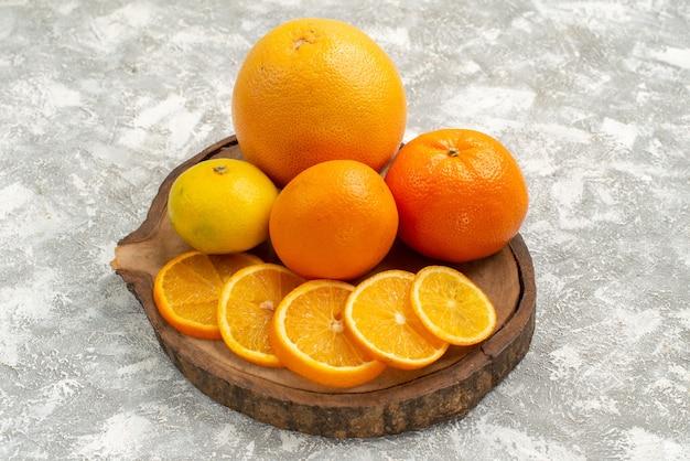 Frische orangen der vorderansicht mit mandarinen auf exotischen tropischen frischen früchten des weißen hintergrundzitrusfruchtes