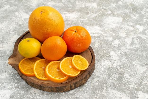 Frische orangen der vorderansicht mit mandarinen auf hellweißem hintergrund zitrus exotische tropische frische frucht