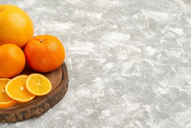 Frische orangen der vorderansicht mit mandarinen auf reifen exotischen tropischen frischen früchten des weißen hintergrundzitrusfruchtes