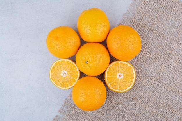 Frische orangen, die auf sackleinen auf weiß liegen.