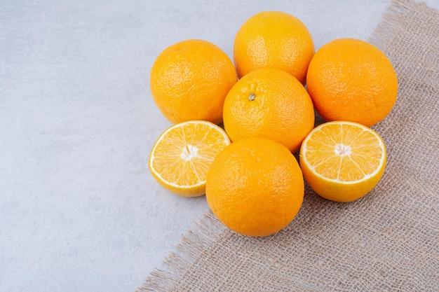 Frische orangen, die auf sackleinen auf weißem hintergrund liegen. foto in hoher qualität