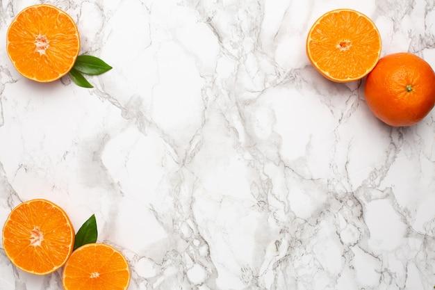 Frische orangen-mandarine auf marmoroberfläche mit copyspace, frucht-flatlay, sommer-minimal und kinfolk-zusammensetzung