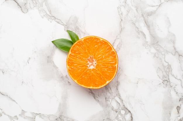 Frische orangen-mandarine auf marmortisch, frucht-flatlay, sommer-minimal und kinfolk-komposition