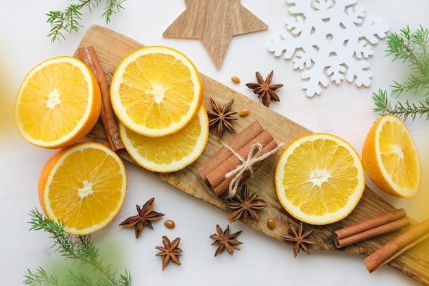 Frische orangen mit anisestars, zimtstangen, wacholderzweigen und aromakerze