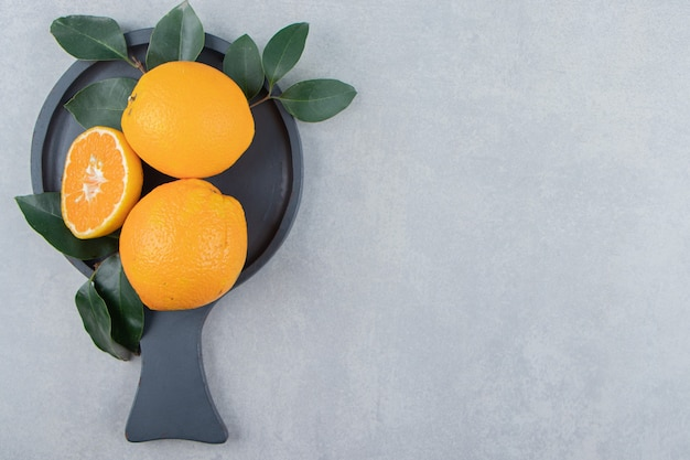 Frische orangen mit blättern auf schwarzem schneidebrett.