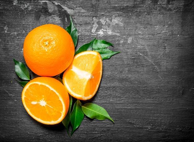 Frische orangen mit grünen blättern auf einer schwarzen tafel