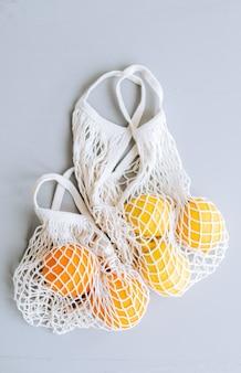 Frische orangen und zitronen in der öko-netz-einkaufstasche auf grau.