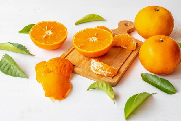 Frische orangenfrucht halbiert auf weißem holzhintergrund