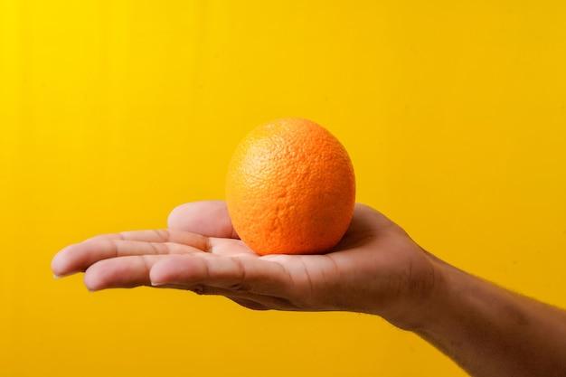 Frische orangenfrucht in der hand halten