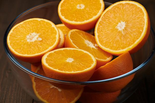 Frische orangenfrüchte ganz und in scheiben geschnitten auf einem holztisch - natürliches und gesundes essen.
