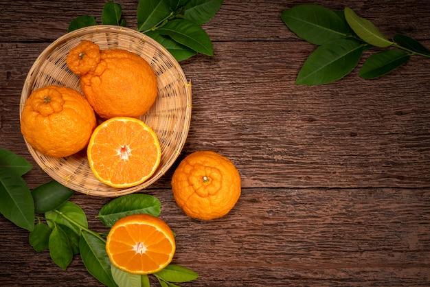 Frische orangenfrüchte im bambuskorb auf holztisch