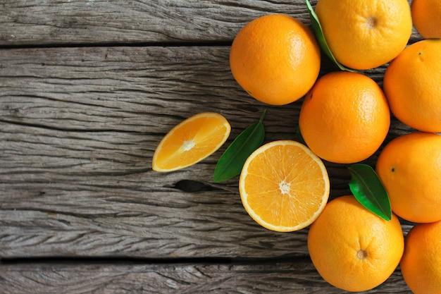 Frische orangenfrüchte mit blättern auf holztisch