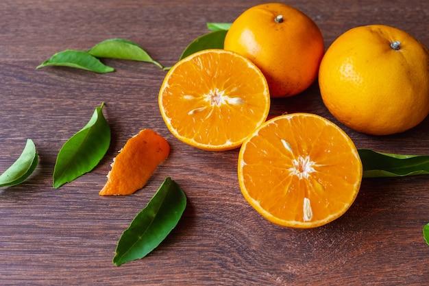Frische orangenfrüchte und orangenfrüchte halbieren auf einem holztisch