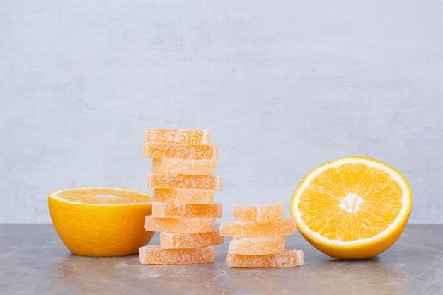 Frische orangenscheiben mit süßen marmeladen auf marmorhintergrund.
