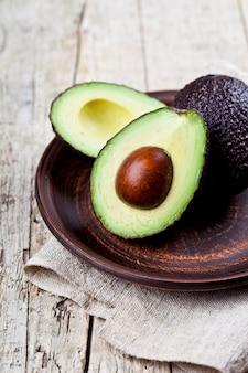 Frische organische avocado auf keramischer platten- und leinenserviette auf rustikalem holztisch