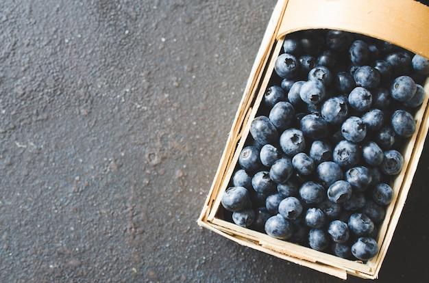 Frische organische blaubeeren im korb auf dunklem beton