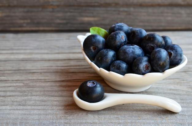 Frische organische blaubeeren in einer weißen schüssel auf altem holz