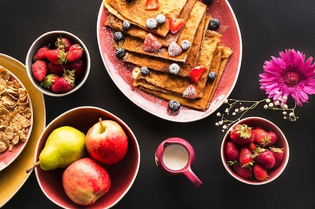Frische organische früchte mit kreppfrühstück auf schwarzem hintergrund