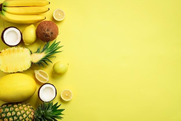 Frische organische gelbe früchte über sonnigem hintergrund. einfarbiges konzept mit banane, kokosnuss, ananas, zitrone, melone.