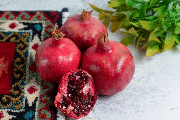 Frische organische granatäpfel über altem traditionellem teppich.