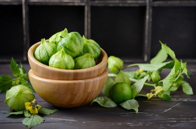 Frische organische grüne tomaten (physalis philadelphica) mit einer schale auf rustikalem holztisch.