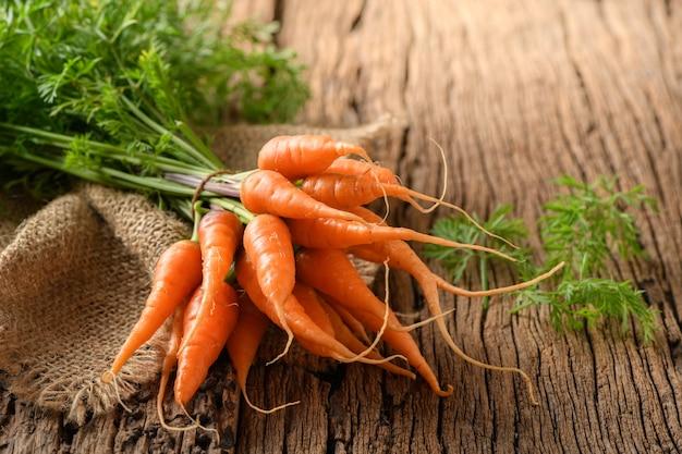 Frische organische karotten mit grünen blättern auf altem hölzernem hintergrund. gemüse. gesundes essen