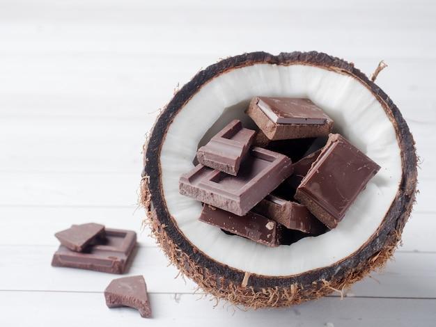 Frische organische kokosnuss gebrochen in zwei teile mit kokosnuss auf einem rustikalen hölzernen hintergrund