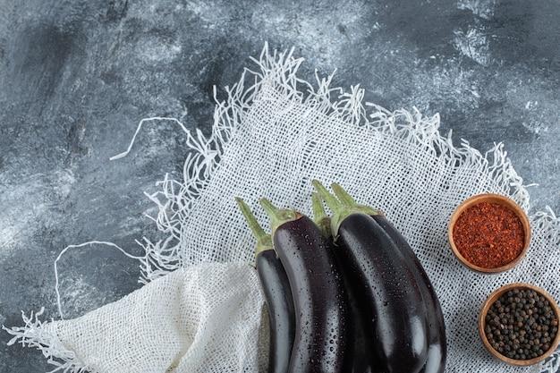 Frische organische lila auberginen mit gewürzen, rotem und schwarzem pfeffer.