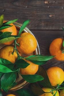 Frische organische mandarinen mit blättern auf rustikalem hölzernem hintergrund. draufsicht.