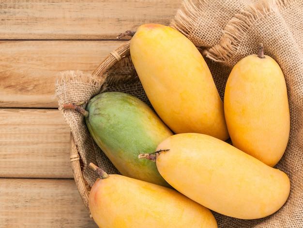 Frische organische mangos gründeten auf hanfsackhintergrund.