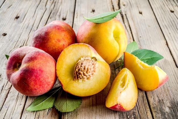 Frische organische pfirsiche auf rustikalem holztisch